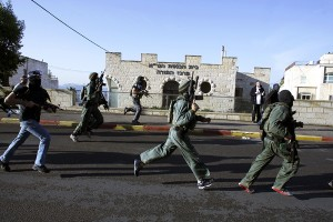 Israeli security personnel run next to a synagogue, where a suspected Palestinian attack took place, in Jerusalem